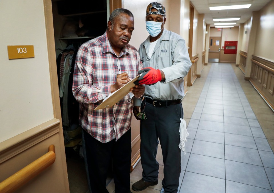<strong>Memphis Housing Authority resident Joe Wilbourn (left) signs paperwork to receive donated face masks from Tedrick Robinson (right) on Thursday, April 23, 2020 at Dr. R.Q. Venson Center Apartment.</strong> (Mark Weber/Daily Memphian)