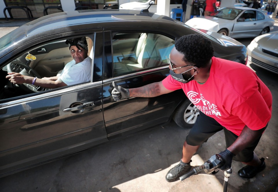 <strong>Brandon Hardin (right) signals that he is finished pumping gas as volunteers from Golden Gate Cathedral, 100 Black Men of Memphis and other local groups come together on April 30, 2020, to give out free gas at the Marathon Station on James Road.</strong> (Jim Weber/Daily Memphian)