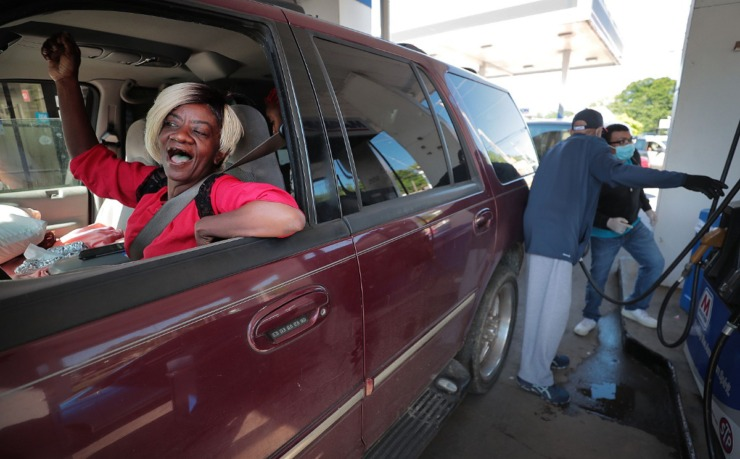 <strong>Anner Sanders (left) enjoys the music while getting her tank filled as volunteers from Golden Gate Cathedral, 100 Black Men of Memphis and other local groups come together on April 30, 2020, to give out free gas at the Marathon Station on James Road.</strong> (Jim Weber/Daily Memphian)