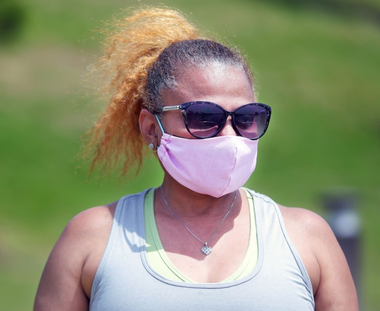 <strong>Taking the recommended safety measure of wearing a mask when going out in public, Cynthia Sharp walks around Hyde Lake in Shelby Farms Park on May 1, 2020.</strong> (Patrick Lantrip/Daily Memphian)