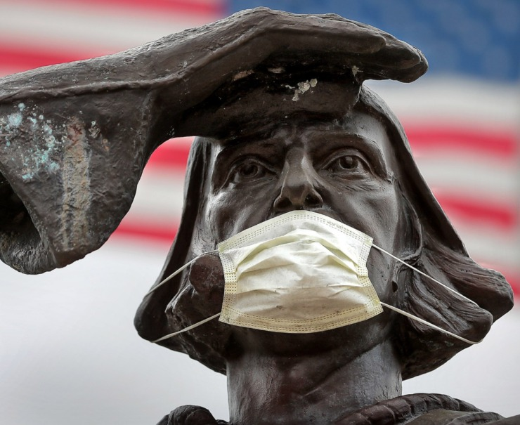 <strong>The bronze statue of famous Italian explorer Christopher Columbus got a little virus protection of his own after someone attached a mask overnight on March 28, 2020, at Marquette Park.</strong> (Jim Weber/Daily Memphian)
