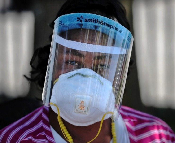 "<strong>Shandra Phillips, known as the ""Sock Lady"" has expanded from her traditional stock of socks to also hawk face masks and surgical gloves on the corner of Cleveland and Poplar on May 1, 2020.</strong> (Jim Weber/Daily Memphian)"