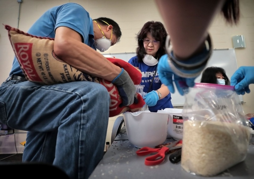 <strong>K.C. Lim (left) and his wife, Lorrean Lim, break down large bags of rice into manageable portions as volunteers from the local Malaysian American community partner with the University of Memphis for a food drive at the International Center on May 2, 2020. Many of the school's international student population have been unable to return home while remotely finishing coursework for the semester.</strong> (Jim Weber/Daily Memphian)