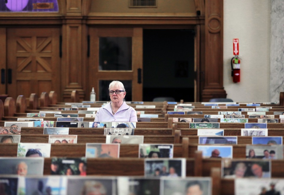 <strong>Bambi Williams, wife of deacon Frank Williams, prays alone at St. Patrick Catholic Church May 3, 2020 while surrounded by the photos of her fellow parishioners. The photos were hung as a way to make the church seem not as empty during its virtual services held during the COVID-19 pandemic.</strong> (Patrick Lantrip/Daily Memphian)