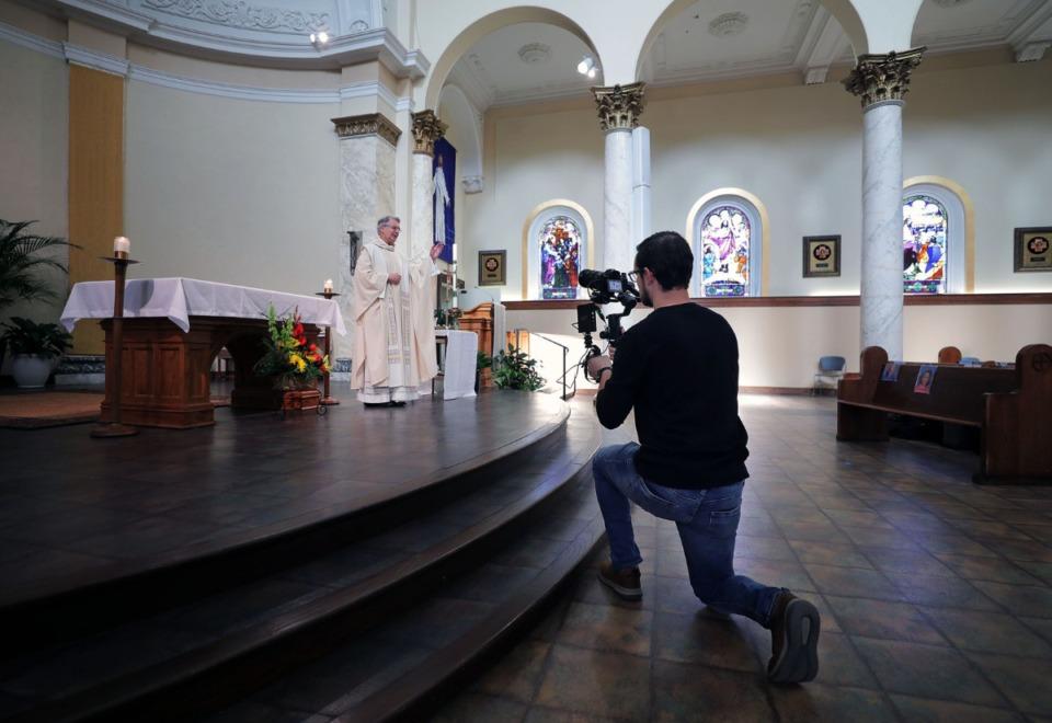 <strong>Brody Kuhar films Monsignor Val Handwerker during a virtual mass at St. Patrick Catholic Church May 3, 2020.</strong> (Patrick Lantrip/Daily Memphian)