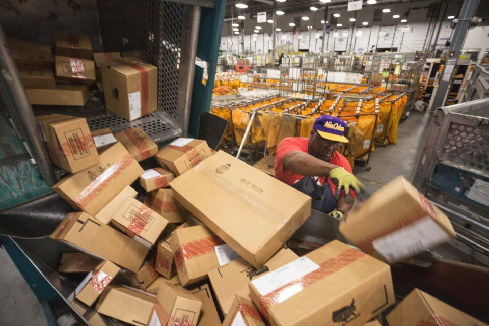<strong>Mail Handler Greg Rogers moves a load of packages to a conveyor belt for further sorting. The U.S. Postal Service will extend the time a customer's mail can be held because of the coronavirus pandemic.</strong> (Daily Memphian file)