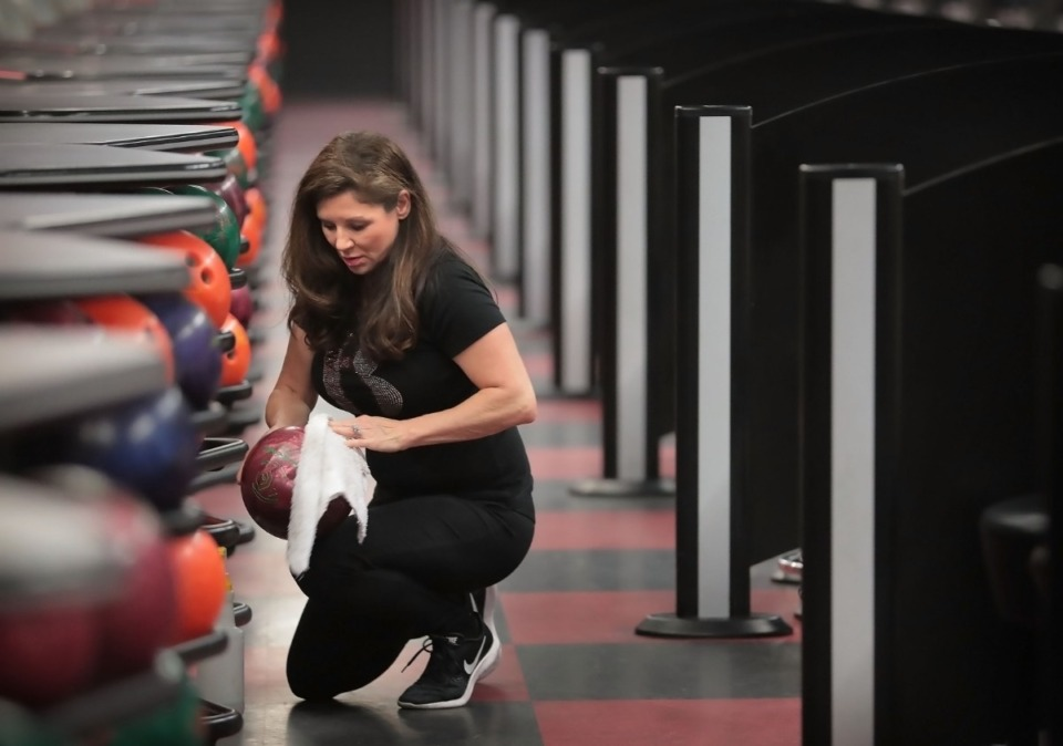<strong>Bowling alleys are among the recreational facilities allowed to reopen Friday, Gov. Bill Lee said during his Tuesday press briefing. Andy B's bowling and entertainment center general manager Traci Sanchez disinfects bowling balls on April 24, 2020 as part of a strict cleaning regimen.</strong> (Jim Weber/Daily Memphian)