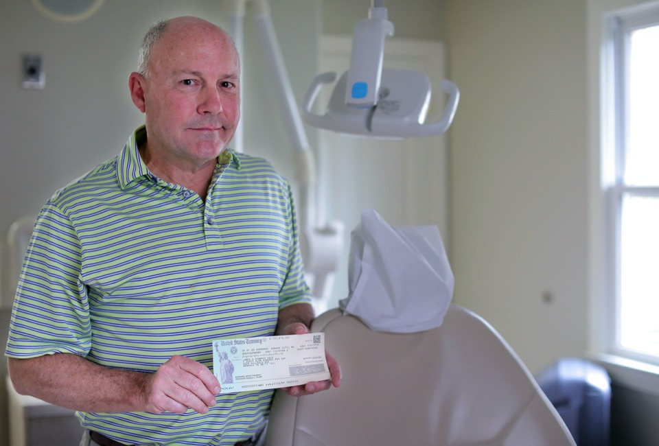 <strong>Dr. Scott Edwards, standing in his East Memphis dentistry office May 5, 2020, holds a $1,200 stimulus check addressed to his late father, James, who died in 2018.</strong> (Patrick Lantrip/Daily Memphian)