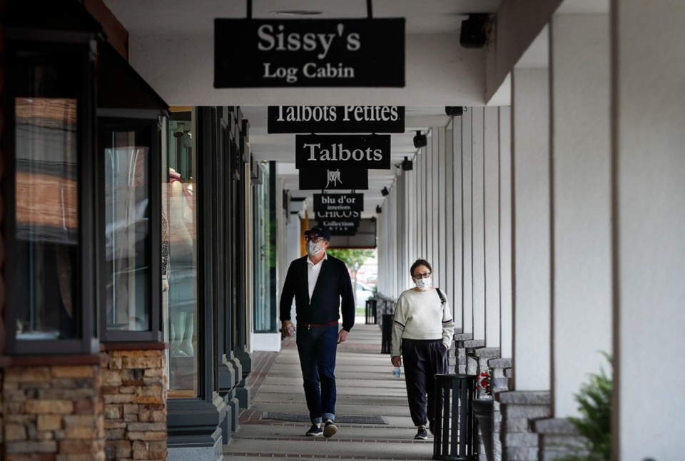 <strong>A couple walks by closed stores at the Laurelwood Shopping Center on Monday, May 4, 2020. Retailers like clothing stores, boutiques and other non-essential businesses that have been closed down for nearly eight-weeks, were allowed to open during Phase One of the city&rsquo;s and county&rsquo;s Back-to-Business Framework.</strong> (Mark Weber/Daily Memphian)
