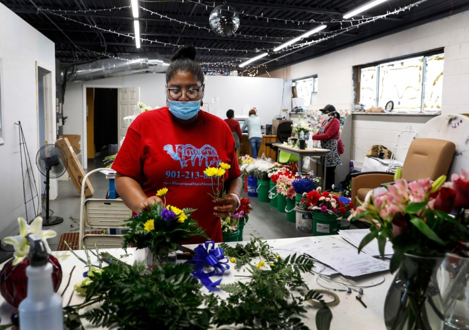 "<strong>Elisa Franklin, owner of Flowers and More, makes a Mother's Day arrangement on Wednesday, May 6, 2020. Franklin ordered flowers for Mother's Day ""on faith."" She's projecting a better-than-typical business due to people sending flowers in lieu of face-to-face visits.</strong> (Mark Weber/Daily Memphian)"
