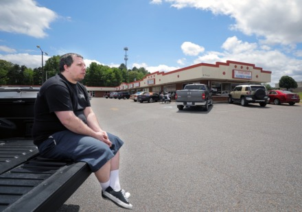 <strong>Mike Wallace social distances on his truck bed while waiting for a haircut outside of a busy Stage Road Barber Shop May 6, 2020.</strong> (Patrick Lantrip/Daily Memphian)