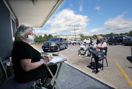 <strong>Pat Jenkins, wife of Stage Road Barber Shop owner Larry Jenkins, helps manage the long wait times outside of the Bartlett barber shop while Rodney Shook, Jill Bailey and Jonathan Pesti wait outside.</strong> (Patrick Lantrip/Daily Memphian)