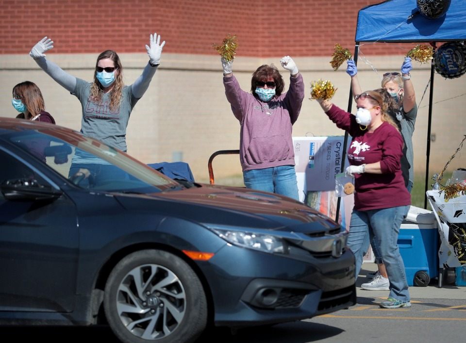 <strong>Collierville High School, staff, teachers, parents and PTSO members cheer for Collierville High School graduates driving through to pick up caps and gowns at the school on May 7, 2020.</strong> (Jim Weber/Daily Memphian)