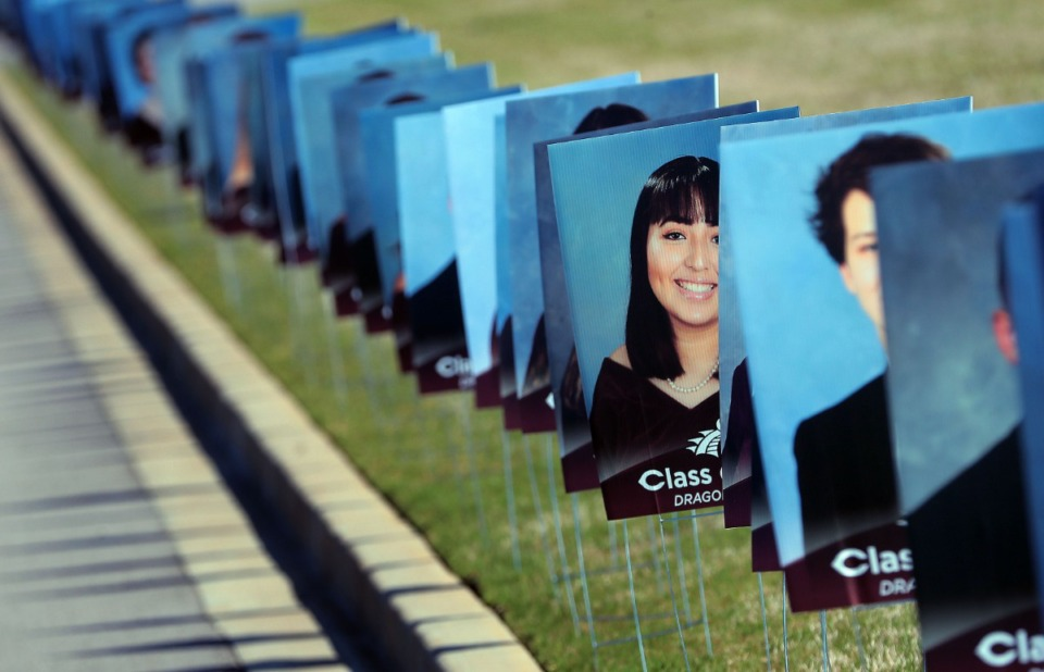 <strong>Cardboard photos of the graduating class decorate the entrance to Collierville High School as graduates drive through to pick up their caps and gowns at the school on May 7, 2020. Collierville teachers, staff and PTSO members turned out to celebrate with the seniors.</strong> (Jim Weber/Daily Memphian)
