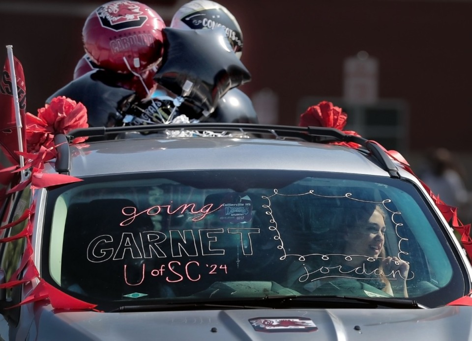 <strong>In her decked out car, Collierville High School graduate Jordan Murphy waves as she drives through to pick up her cap and gown at the school on May 7, 2020. Collierville teachers, staff and PTSO members turned out to celebrate with the seniors.</strong> (Jim Weber/Daily Memphian)