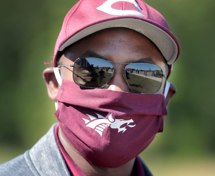 <strong>Collierville High School Principal Roger Jones III masks up with school spirit as staff, teachers, parents and PTSO members cheer for Collierville High School graduates driving through to pick up caps and gowns at the school on May 7, 2020.</strong> (Jim Weber/Daily Memphian)