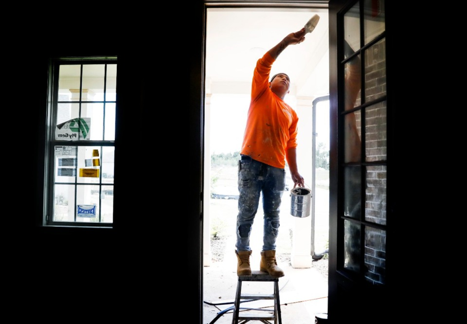 <strong>Noel Morales paints door trim during construction on a White Oak neighborhood home on Thursday, May 7, 2020 in Arlington.</strong> (Mark Weber/Daily Memphian)