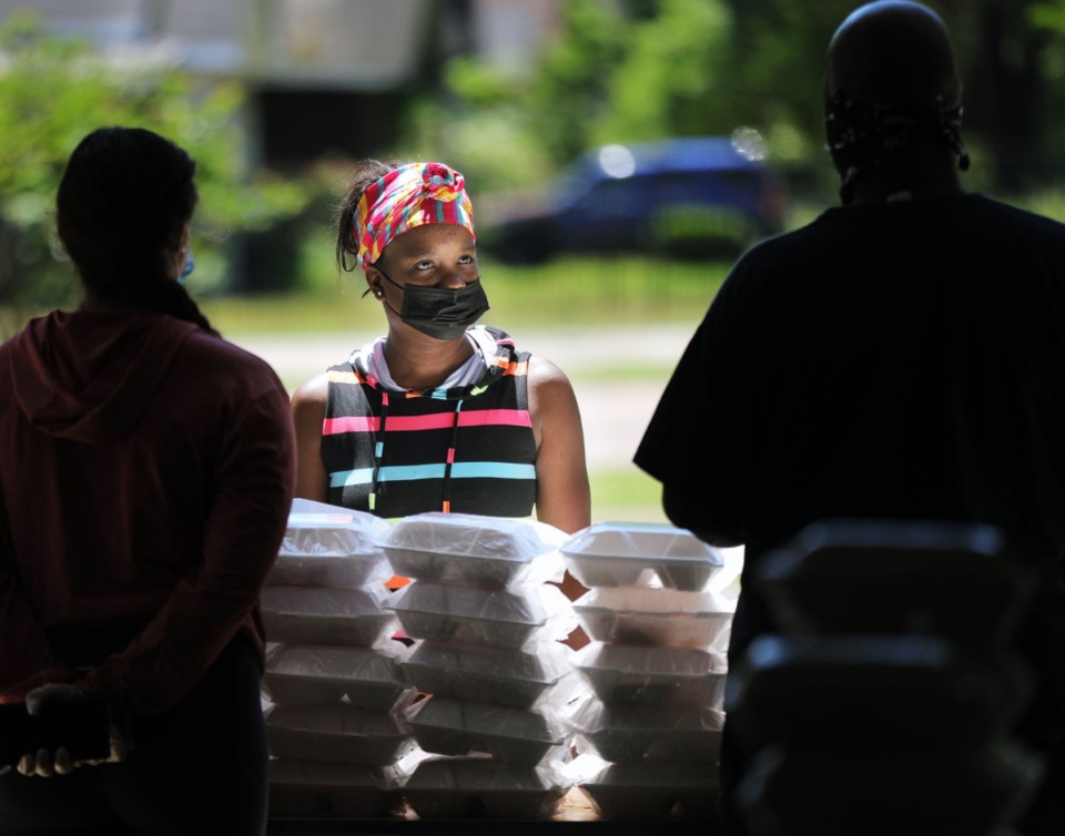 <strong>Latosha Earl picks up several meals provided by the YMCA at Christ Missionary Baptist Church in South Memphis on Thursday, May 7. The YMCA's emergency food distribution program has been distributing thousands of meals a day to Memphians in need.</strong> (Patrick Lantrip/Daily Memphian)