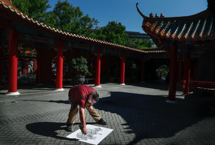 <strong>Memphis Zoo maintenance team member Josh Fortney spray paints one-way signs inside the China Pagoda on Monday, May 11, 2020. The Zoo, closed since the outbreak of COVID-19, will reopen on Wednesday with new social distancing measures that include guiding guests in one direction as they tour the zoo.</strong> (Mark Weber/Daily Memphian)