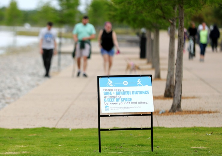 <strong>Signs reminding people to social distance during the ongoing COVID-19 pandemic are posted in Shelby Farms Park, as seen May 11, 2020.</strong> (Patrick Lantrip/Daily Memphian)