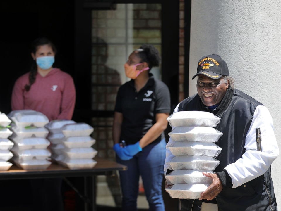 <strong>Larry Duncan (right ) picks up several meals provided by the YMCA at Christ Missionary Baptist Church in South Memphis May 7, 2020. The YMCA's emergency food distribution program has been passing out thousands of meals a day to Memphians in need.</strong> (Patrick Lantrip/Daily Memphian)