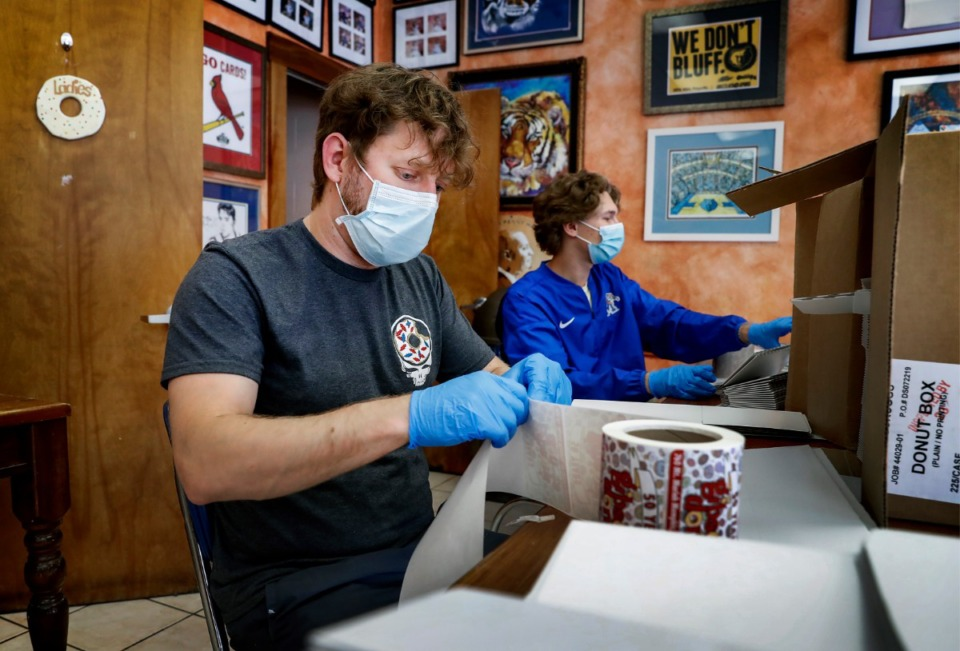 <strong>Gibson&rsquo;s Donut employees Will Geater (left) and Tyler Stover place labels on to-go boxes on Thursday, May 14, 2020.</strong> (Mark Weber/Daily Memphian)