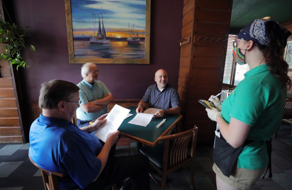 <strong>Half Shell employee Katelyn Pfahler takes the order of (from right) Jim Henry, Dennis Russell and Wally Alexander May 4, 2020.</strong> (Patrick Lantrip/Daily Memphian)