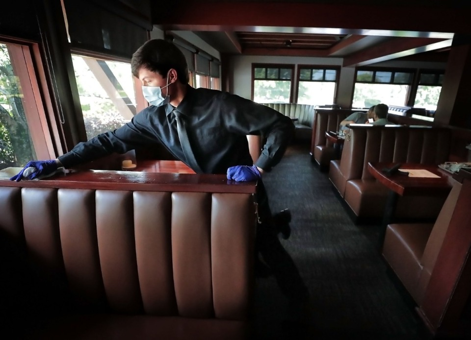 <strong>Brandon Gibson disinfects booths and tables after they are vacated as staff and servers at J. Alexander's Redlands Grill reopen the Cordova restaurant.</strong> (Jim Weber/Daily Memphian)