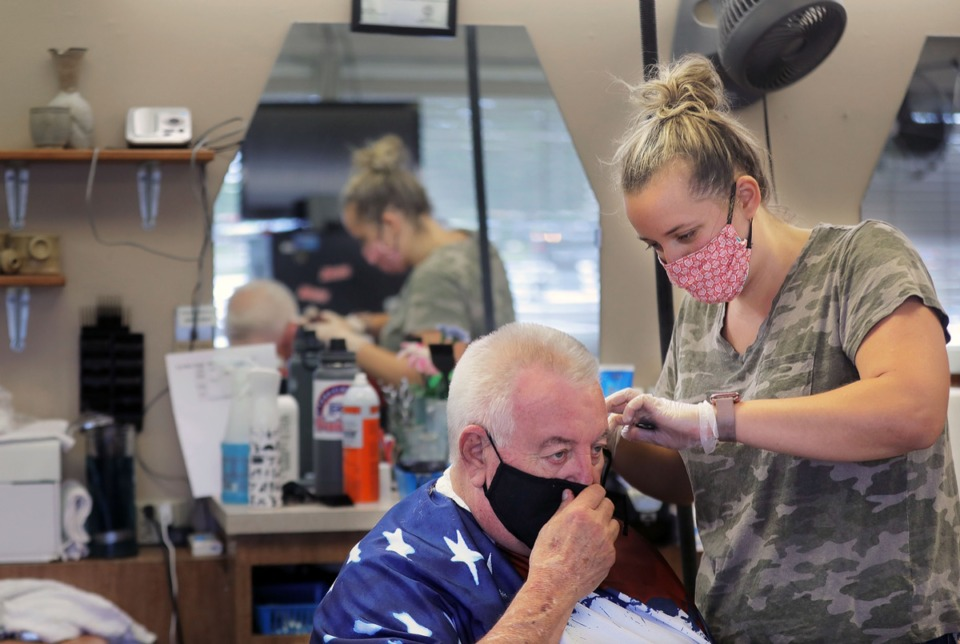 <strong>Sam Lingua (left) gives Robert Frailey Sr. a haircut at Stage Road Barber Shop in Bartlett May 6, 2020. Masks are very m uch in use there.</strong> (Patrick Lantrip/Daily Memphian file)