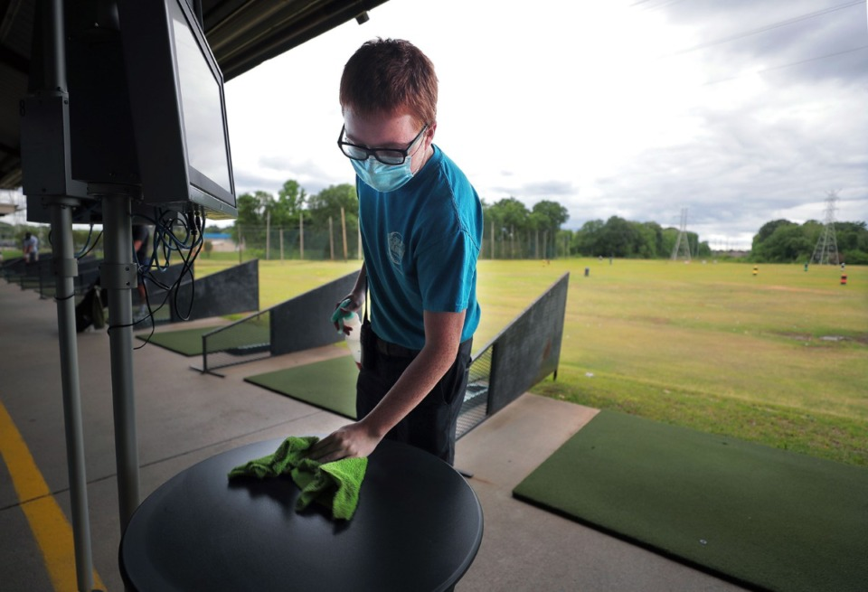 <strong>Jacob Bell wipes down the tables near the driving range between customers at Golf and Games Family Park May 19, 2020.</strong> (Patrick Lantrip/Daily Memphian)