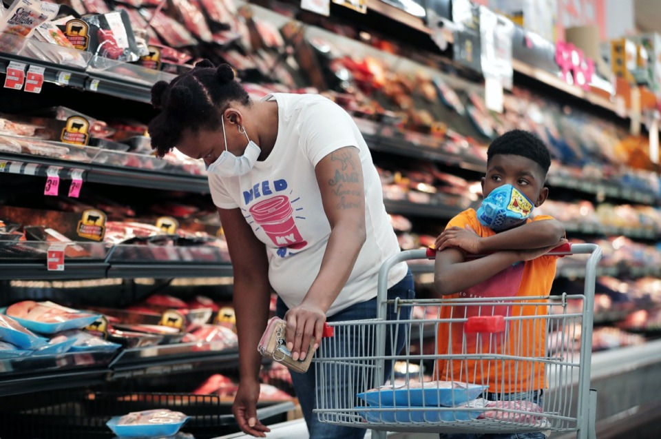 <strong>Ardarius Lowrey daydreams while his mother, Shennika Caples, browses the meat section of Superlo Foods in East Memphis on May 22, 2020, in preparation for a Memorial Day barbecue.</strong> (Patrick Lantrip/Daily Memphian)
