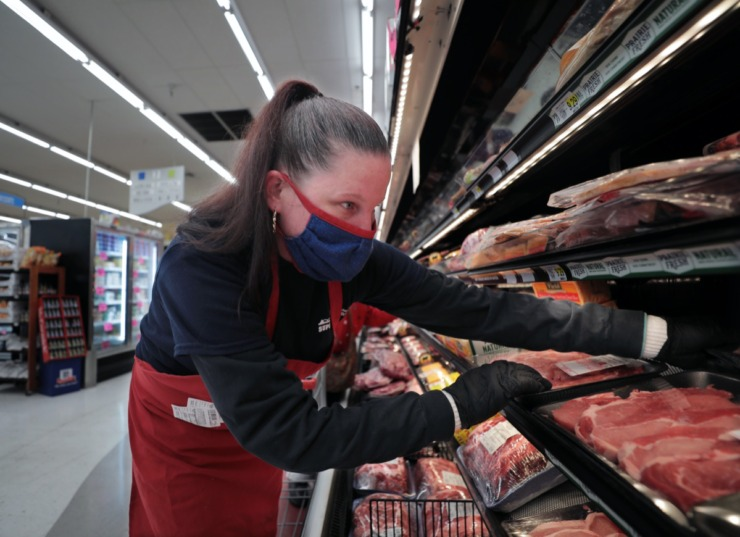 <strong>Christina Grover stocks the meat section of Superlo Foods in East Memphis May 22, 2020.</strong> (Patrick Lantrip/Daily Memphian)