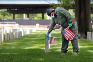 <strong>Army veteran and Memphis National Cemetery employee Howard Hurst places American flags near the gravesites of fallen service members on May 22, 2020, in preparation for Memorial Day.&nbsp;There will be no public events at the cemetery off Jackson Avenue this year</strong>. (Patrick Lantrip/Daily Memphian)