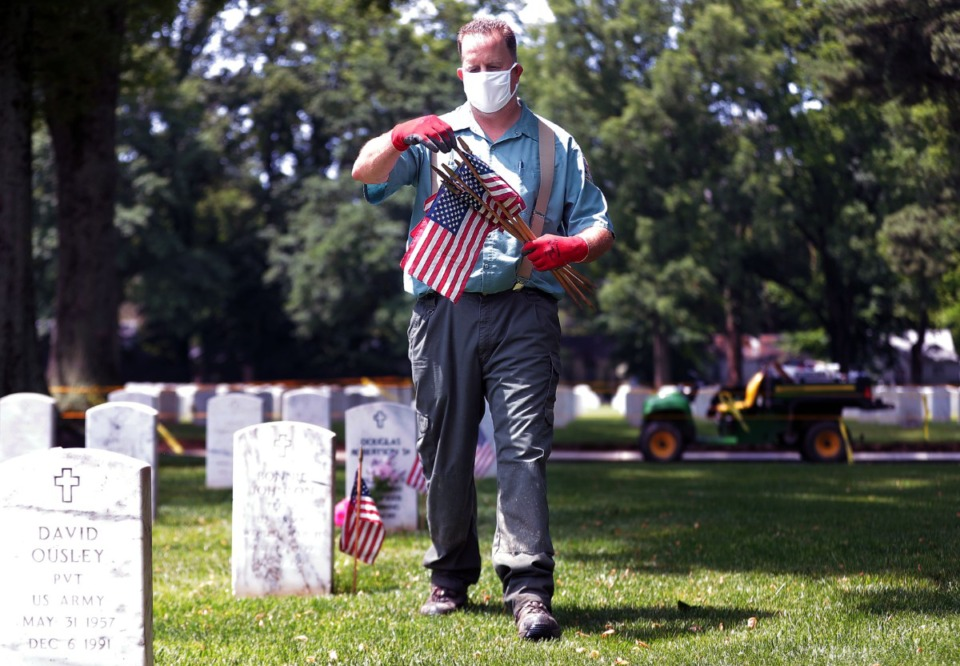 <strong>U.S. Navy vet Michael Sinnock places American flags near the gravesites of fallen service members at the Memphis National Cemetery May 22, 2020, in preparation for Memorial Day.</strong> (Patrick Lantrip/Daily Memphian)