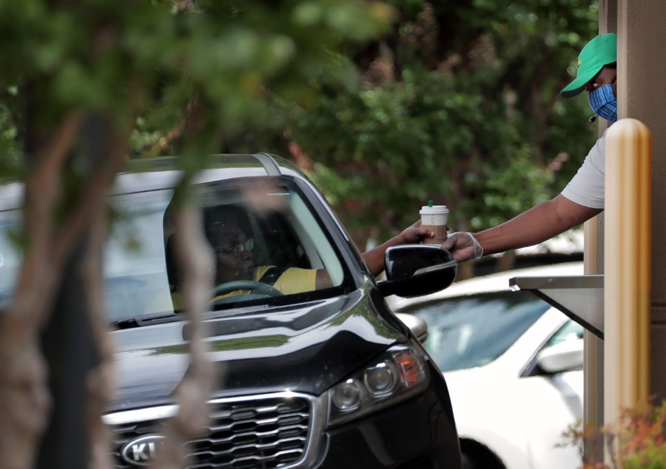 <strong>A Starbucks employee hands out a drink to a customer at the 1850 Union Ave. location May 20, 2020. Although many Starbucks drive-thru locations have remained open through the pandemic, sales have been hurt and the company has asked landlords for accommodations in rent.</strong>&nbsp;(Patrick Lantrip/Daily Memphian)