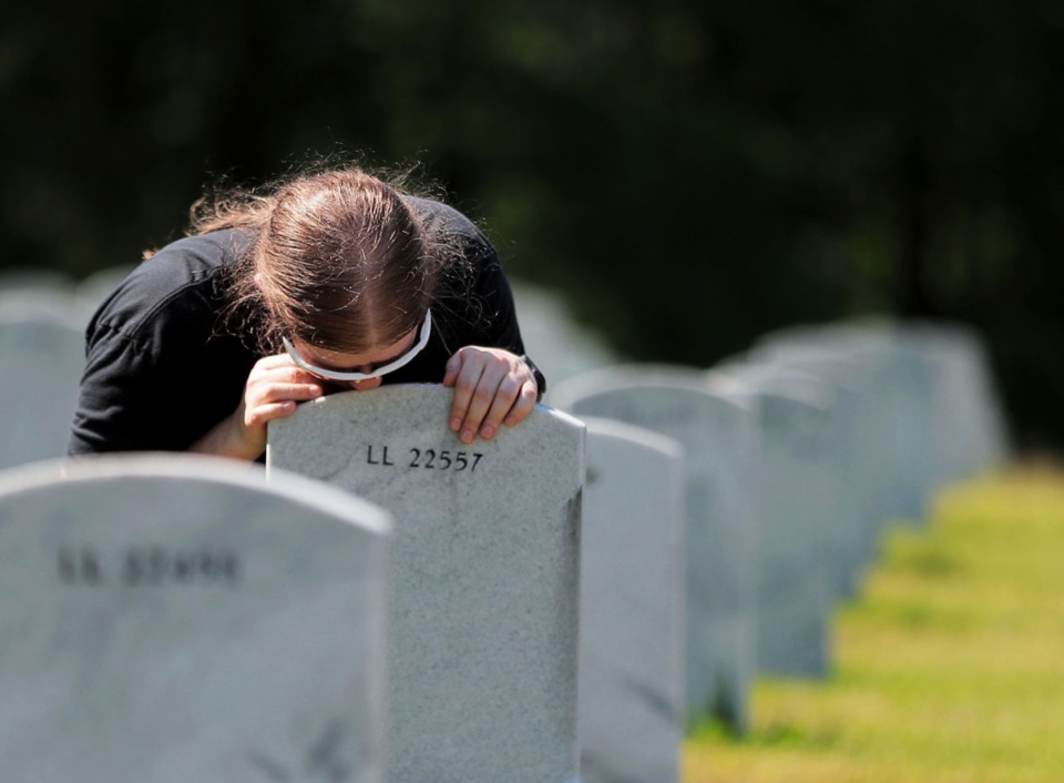 "<strong>Heather McLean kisses the headstone of her friend's mother and Marine Corps veteran Dorothea ""Dottie"" Castillo at the West Tennessee State Veterans Cemetery on Memorial Day May 25, 2020</strong>. (Patrick Lantrip/Daily Memphian)"