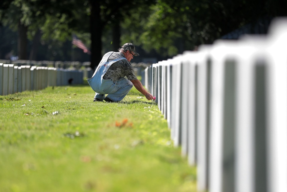 <strong>Alton Davis lays a single flower on the grave of his good friend, Marine sergeant Keith Wilson, at Memphis National Cemetery on Memorial Day May 25, 2020</strong>. (Patrick Lantrip/Daily Memphian)