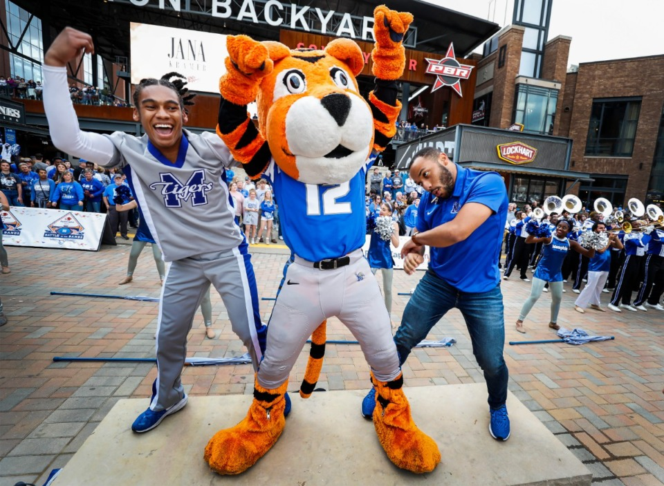 <strong>University of Memphis mascot Pouncer (middle) dances with Michael McGee (left) and Robby Dockery (right) during the Cotton Bowl last December in Arlington, Texas.</strong> (Mark Weber/Daily Memphian file)