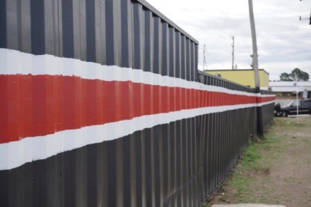 <strong>Mot C Wheels, 4599 Millbranch, painted and straightened the alignment of the eight shipping containers it uses as a security fence and for storing tires.</strong> (Tom Bailey/Daily Memphian)