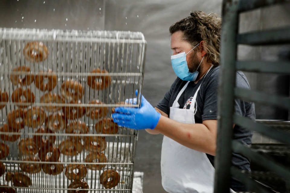 <strong>Gibson&rsquo;s Donuts employee Matt Kennedy flips a rack of doughnuts on Thursday, May 14, 2020. The famous Memphis shop closed in late March due to the COVID-19 outbreak and reopened to customers on May 15.</strong> (Mark Weber/Daily Memphian)