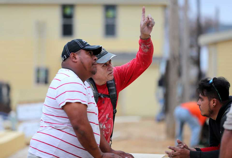 <strong>Juan Jose (center) works out construction plans for the Mason Homes on Fourth development with Isai Ozuna (left) and Leiber Ozuna (right) of O &amp; C Construction. COGIC and city of Memphis leaders came together Nov. 30, 2018, to celebrate the formal opening of the residential development along E.H. Crump Boulevard.</strong> (Houston Cofield/Daily Memphian)