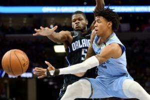 <strong>Memphis Grizzlies guard Ja Morant (12) passes the ball as Orlando Magic center Mo Bamba (5) defends during the first half of an NBA basketball game Tuesday, March 10, 2020, in Memphis, Tenn.</strong> (AP Photo/Brandon Dill)