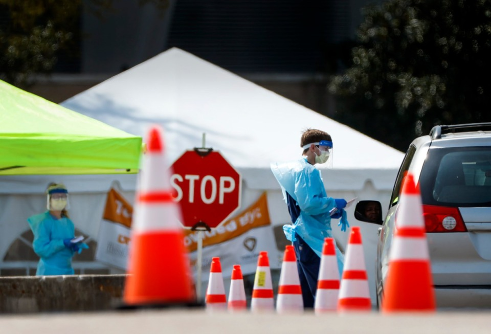<strong>Staff and students from the University of Tennessee Health Science Center work with the Shelby County Health Department on April 1 at a drive-thru COVID-19 testing site at the Memphis Fairgrounds.</strong> (Mark Weber/Daily Memphian file)