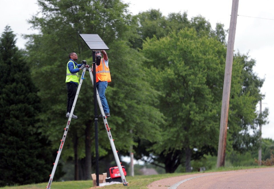 <strong>Christian Pratt (left) and Tommy Owens with Flock Safety install a security camera near the intersection of U.S. Highway 64 and Davies Plantation Road on May 19.</strong> <strong>The solar-powered, motion-activated cameras are able to record the make, model, color, and license plate state and number with a timestamp for vehicles that pass by.</strong> (Patrick Lantrip/Daily Memphian)