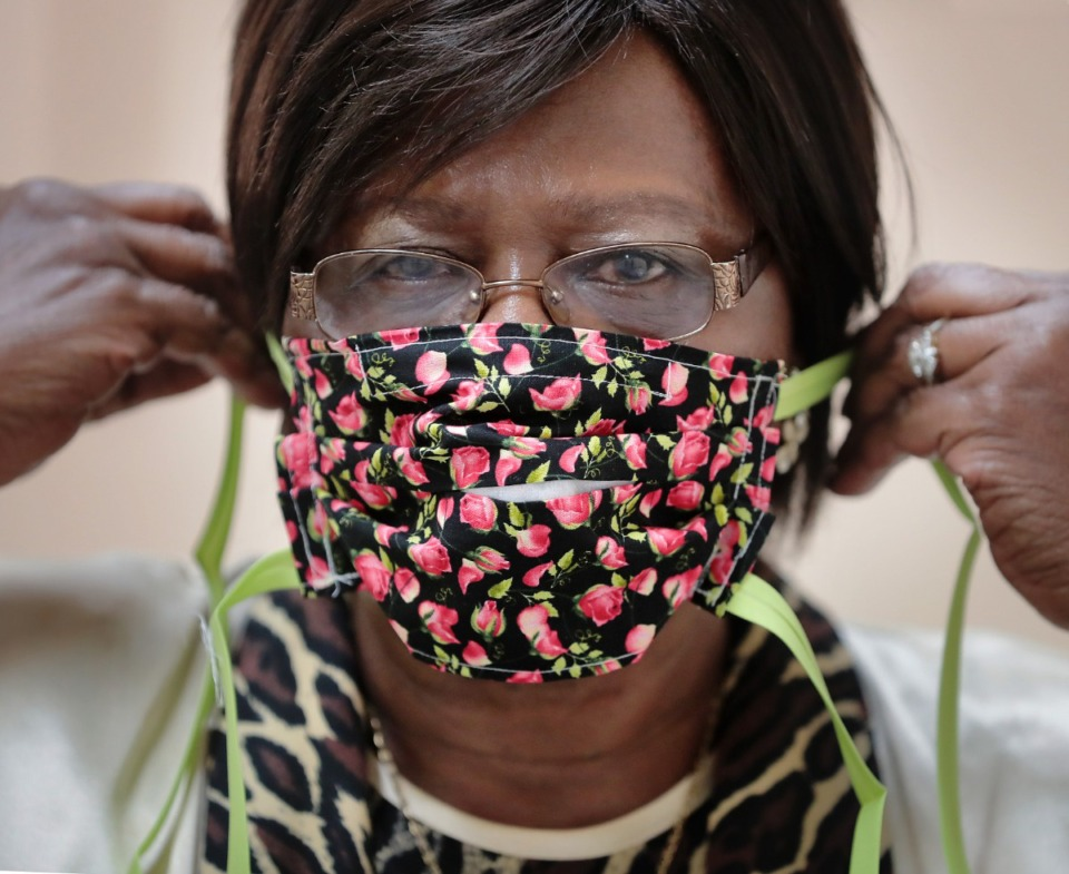 <strong>Corrections program specialist Gloria Phillips shows a finished product as inmates at the Shelby County Correctional Center learn how to make fabric masks on April, 17, 2020.</strong> (Jim Weber/Daily Memphian file)