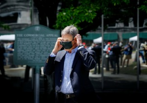 <strong>Tennessee Gov. Bill Lee puts on his face mask during a press conference outside the former Commercial Appeal building on Monday, May 18, 2020. The former newspaper building has been turned into an emergency hospital that could house COVID-19 patients. </strong>(Mark Weber/Daily Memphian)