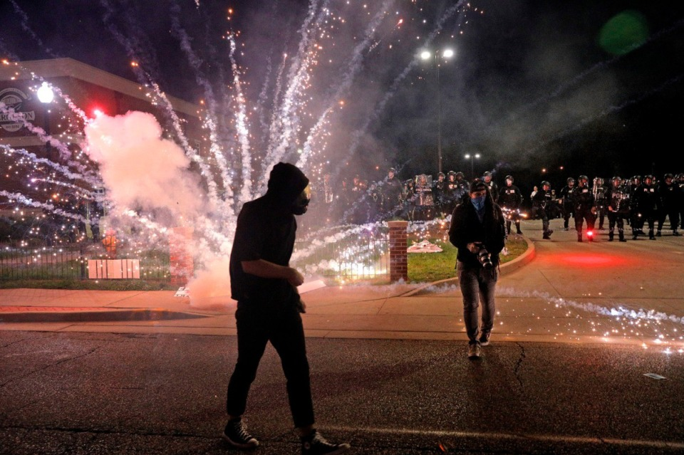 <strong>In the St. Louis suburb of Ferguson, protesters throw fireworks at the police department on Sunday, May 31, 2020.</strong> (Christian Gooden/St. Louis Post-Dispatch via AP)