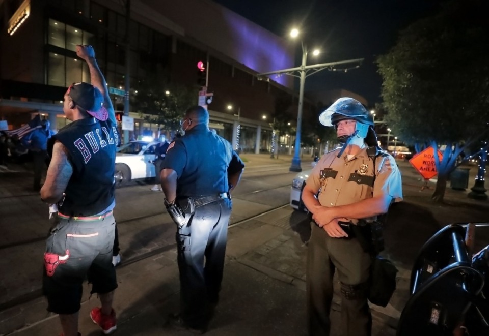 <strong>A protestor convinces a Tennessee State Trooper to put down his baton as the crowd peacefully passes down Poplar Avenue.</strong> (Patrick Lantrip/Daily Memphian)
