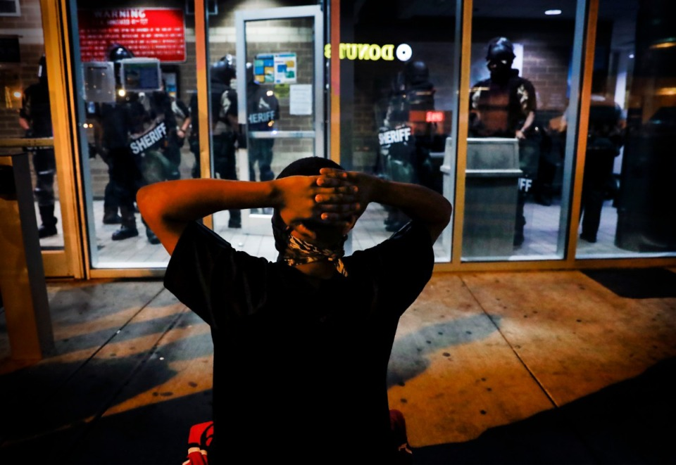 <strong>A protester kneels in front of Memphis Police officers, who are inside the Shelby County Criminal Justice Center in Memphis on Monday, June 1, 2020, during a protest over the Minneapolis killing of George Floyd.</strong> (Mark Weber/Daily Memphian)