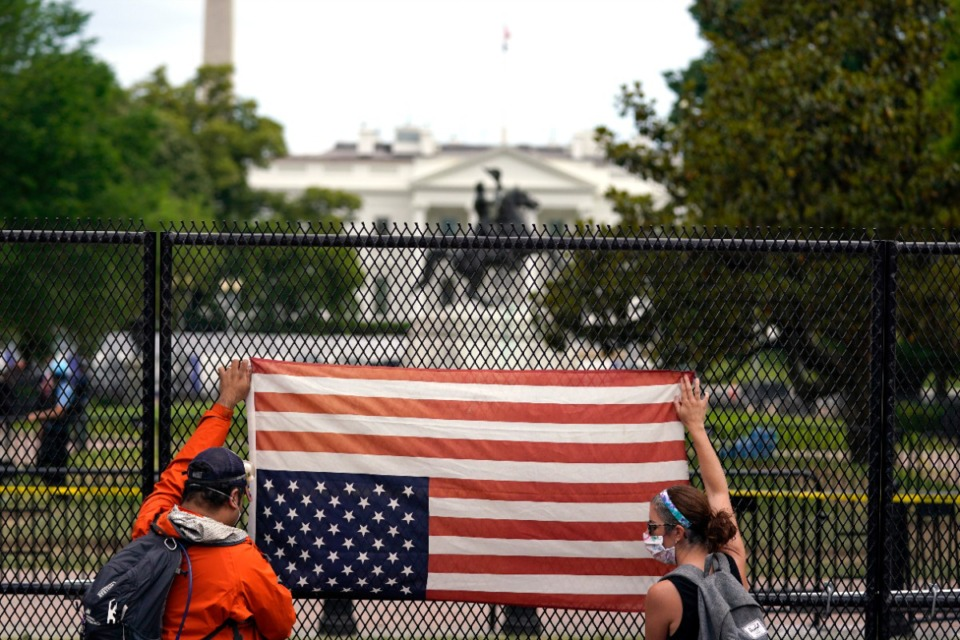 <strong>Demonstrators hold an American flag upside-down in front of fencing near the White House in Washington on Tuesday, June 2, as they protest the death of George Floyd in Minneapolis. The Tennessee National Guard is sending 1,000 troops to the nation&rsquo;s capital to quell potential rioting during protests.</strong> (Evan Vucci/Associated Press)